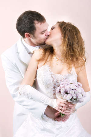 Young couple kissing in wedding wear with bouquet of chrysanthemum. Special pink toned photo f/x photo