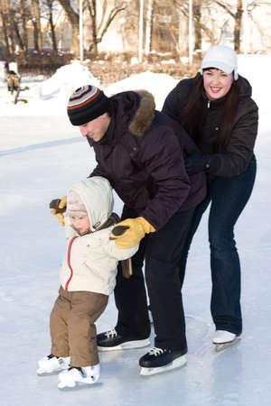 patinaje sobre hielo: Recreaci�n de Invierno. Familia de patinaje en pista. Atenci�n se centra en la cara de ni�o, el padre y la madre es un poco borrosa-moci�n