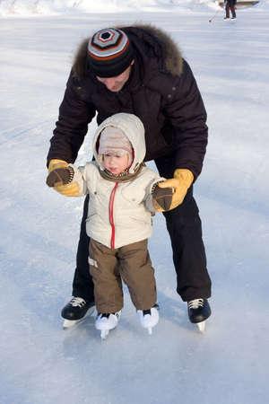 patinando: Recreaci�n de Invierno. Padre y ni�o patinaje en pista. Atenci�n se centra en la cara de ni�o  Foto de archivo