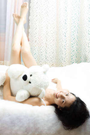Beautiful girl in the bed with teddy-bear, smiling. With copy-space photo