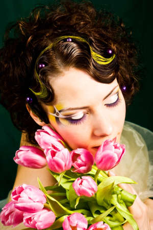 Portrait of young bride with artistic makeup in wedding wear photo