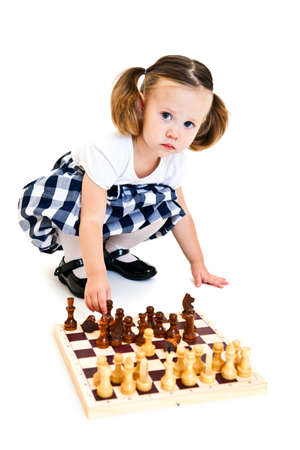 Cute little girl with ponytails playing chess. Isolated on white photo