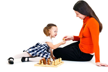 Cute little girl with ponytails playing chess with her mother. Isolated on white photo