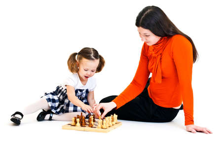 ponytails: Cute little girl with ponytails playing chess with her mother. Isolated on white