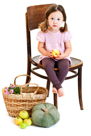 ponytails: Cute little girl with ponytails eating apple. Isolated on white