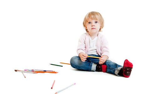 Cute little girl with pencils on the floor. Isolated on white photo
