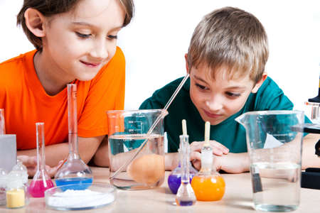 Two little boys doing biochemistry research at the lab. Isolated on white Stock Photo - 17334467
