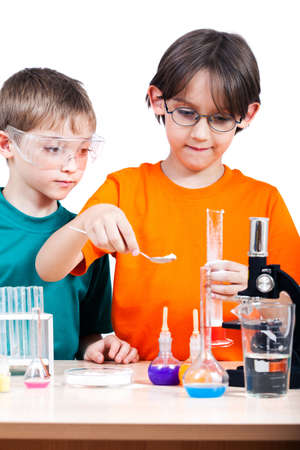 Two little boys doing biochemistry research at the lab. Isolated on white photo