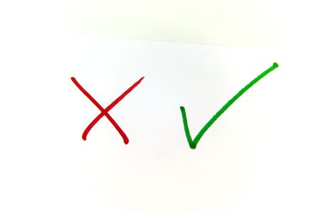 positiv: A close up view of a check mark and a cross over white Stock Photo