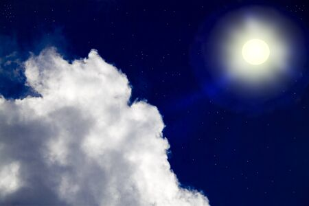Night sky. The moon in the starry sky illuminates the clouds photo