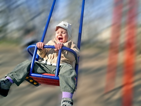 Enthusiastic kid on a swing Stock Photo