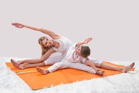 sports form: Una giovane e bella madre, le pratiche yoga con suo figlio Archivio Fotografico