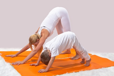 A beautiful young mother practices yoga with her son Stock Photo