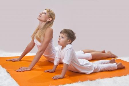 sports form: Una giovane madre bella pratica yoga con il figlio