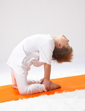 Childrens yoga. The little boy does exercise. Stock Photo