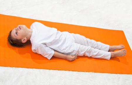 Childrens yoga. The little boy does exercise.