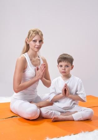 A beautiful young mother practices yoga with her son  photo