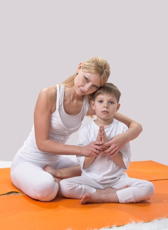 A beautiful young mother practices yoga with her son Stock Photo - 11950389