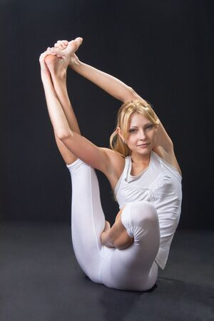 Young beautiful girl is professionally engaged in yoga  photo