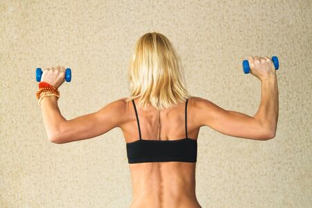 Beautiful athletic muscular woman working with two dumbbells photo