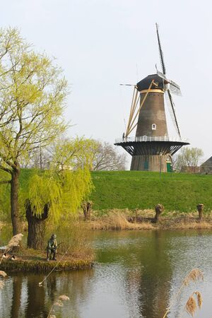gorinchem: Statue of the fisherman on the background of a windmill in Gorinchem. Netherlands