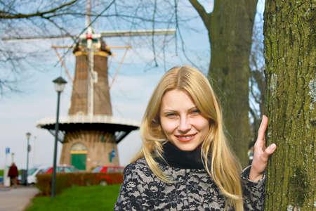dutch girl: Girl near  windmill in  Dutch town of Gorinchem. Netherlands Stock Photo