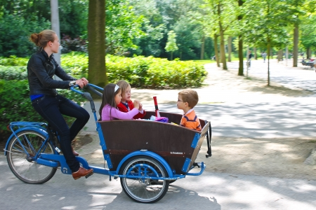 Young girl transporting children in the cart . Amsterdam. Netherlands Editorial