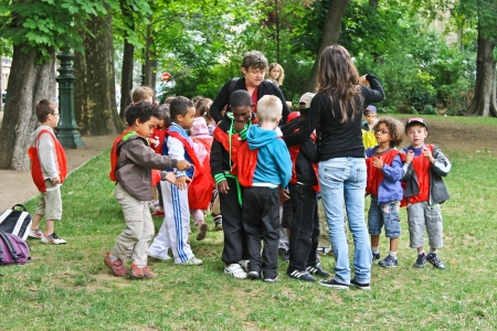 PARIS, FRANCE - JULY 10: group of french unidentified kids with two teachers in the sity park on July 10, 2012 in Paris, France.