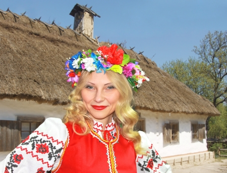 Beautiful Ukrainian girl in national clothes near the rural house photo