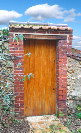 Wooden door in an old stone fence photo