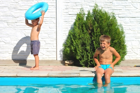 Two brothers near a swimming pool at summer vacation photo