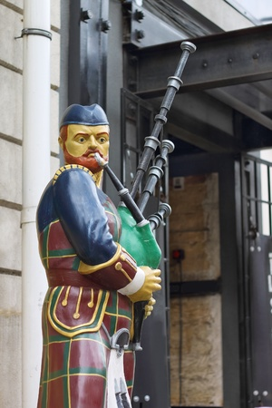 irish cities: Bagpiper statue near the entrance to the building. Stock Photo