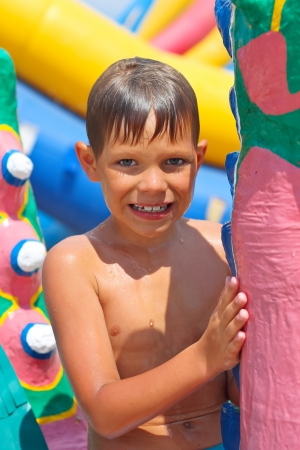 Smiling kid at a water park near the inflatable slides
