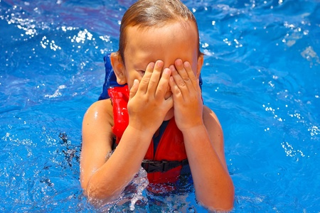 Kid in the swimming pool  covered his face with his hands photo