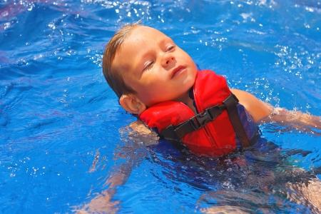 Tranquil kid in vest floating on her back at the pool aqua park photo