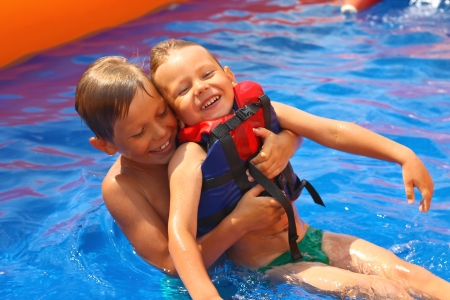 Two brothers in swimming pool at the water park photo