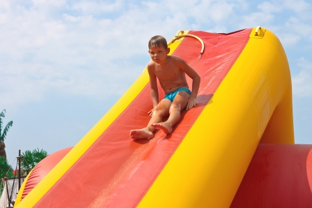 Enthusiastic kid on slide in the waterpark  Stock Photo