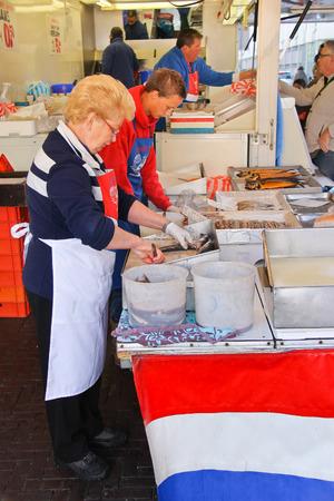 DORDRECHT, THE NETHERLANDS - SEPTEMBER 28: Workers cut up fish for sale at a market on September 28, 2013 in Dordrecht, Netherlands