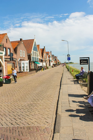 volendam: VOLENDAM,THE NETHERLANDS - JULY 7, 2012 : Tourists in the port  Volendam. Volendam is an international tourist attraction that introduces visitors to the life of the Dutch fishermen in the old days.