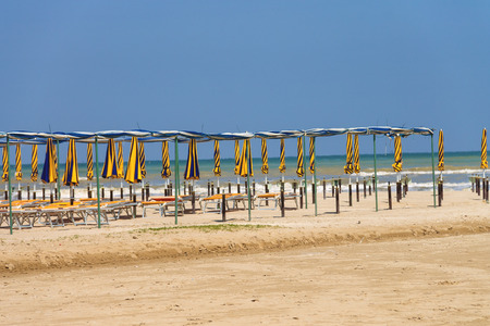 Rows of umbrellas and deck chairs on a sunny beach photo