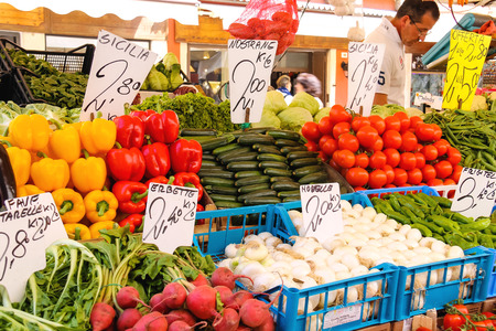 the merchant of venice: VENICE, ITALY - MAY 06, 2014: Seller near a counter with vegetables on a market in Venice, Italy Editorial