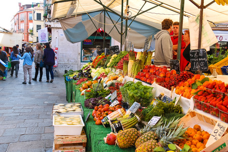the merchant of venice: VENICE, ITALY - MAY 06, 2014: People near a counter with vegetables on a market in Venice, Italy Editorial