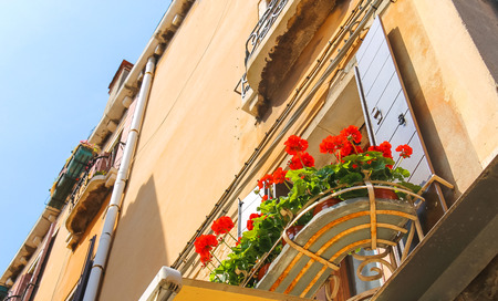 Flowers at the window of the Italian home photo