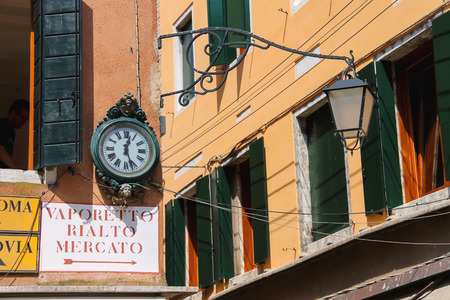corner clock: VENICE, ITALY - MAY 06, 2014: Clock and lantern hanging on a corner the house in Venice, Italy