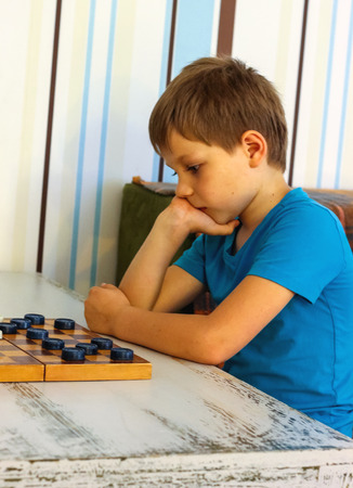 Pensive boy during a game of checkers photo