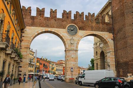 VERONA, ITALY - MAY 7, 2014:  People and vehicles near the medieval city gates on Portoni della Bra. Verona, Italy