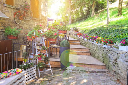 Flowers and bicycle in the external design of the outdoor restaurant in San Marino Stock Photo