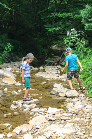 Two kids playing near a mountain stream Stock Photo