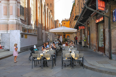italy: Bologna, Italy - August 18, 2014: People relax behind little tables of the restaurant Zerocinquantuno on Via DePignattari in Bologna. Italy