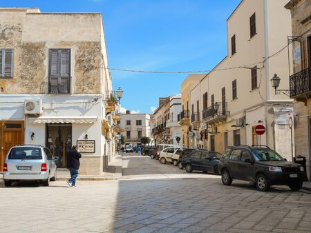 Favignana, Sicily, Italy - March 10, 2015: People and cars on the Piazza Europa in Favignana